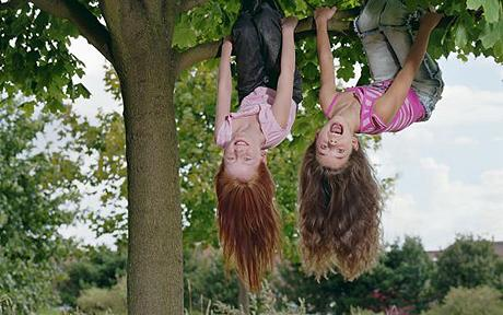 Two girls (8-10) hanging upside down in tree, smiling, portrait